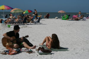 spring breakers on beach playing guitar