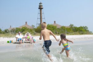 children running toward parents sitting on beach